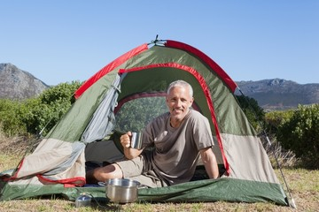 Happy camper holding mug outside his tent