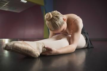 Ballerina sitting and bending forward