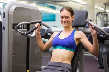 Fit smiling brunette using weights machine for arms