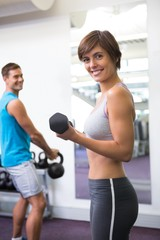 Fit couple lifting weights together smiling at camera