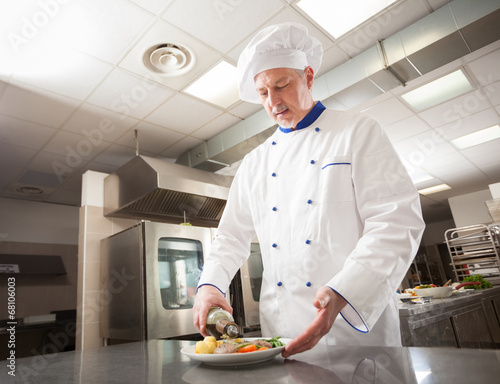 Male chef decorating a dish