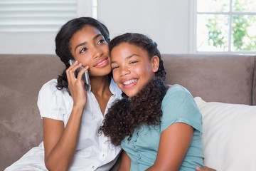Happy mother and daughter using smartphone together on sofa