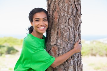 Pretty environmental activist hugging tree