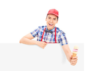 Male vendor holding an ice cream behind a panel