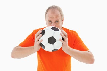 Nervous football fan holding ball