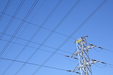 Upper Section of Pylon with Powerlines Against Blue Sky