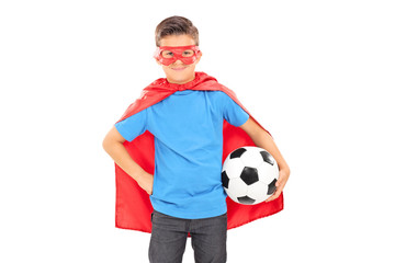 Boy in superhero costume holding a football