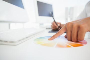 Designer working at desk using a colour wheel
