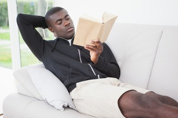 Casual man sitting on his sofa reading a book