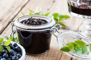 Blueberry jam in glass jar on wooden table