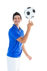 Football player in blue spinning ball
