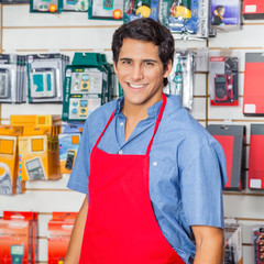 Handsome Salesman In Red Apron Smiling At Hardware Shop