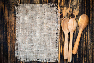 Burlap and rural kitchen utensils on wooden table  view from top