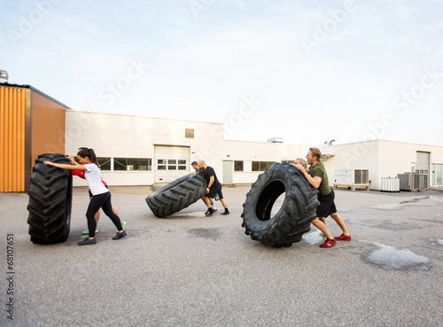 Foto op Plexiglas Fitness Athletes Doing Tire-Flip Exercise Outdoors