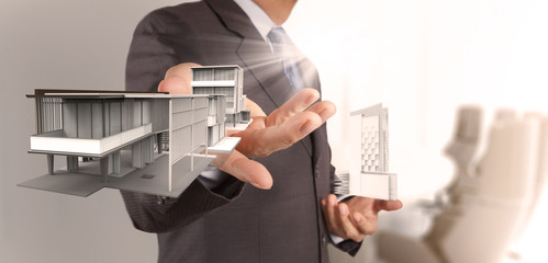 businessman hand presents house model on modern computer