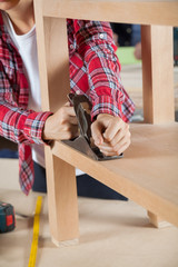 Carpenter Using Planer On Wooden Shelf