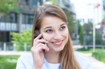 Attractive woman with blond hair laughing at phone