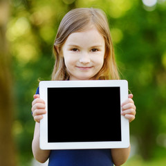 Happy child holding tablet PC outdoors