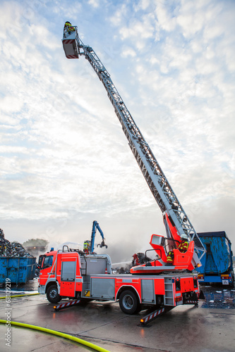 Leinwanddruck Bild Fire truck with a cherry picker or elevated cage