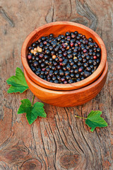 Sweet, black currant and green leaves in wooden bowl.