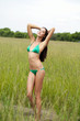 Beautiful model in a green bathing suit standing in the summer f