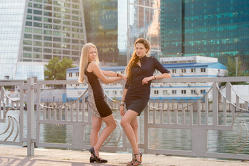 Two young beautiful girls in dress stroll along the river on the