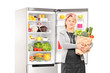 Woman with bag of vegetables in front of a fridge