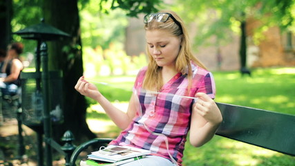 Teenage girl listen to the music on smartphone in city park