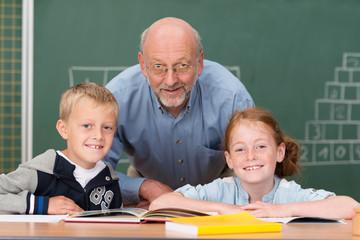 lächelnder älterer lehrer mit zwei schülern im klassenzimmer