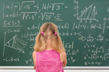 kleines mädchen schaut auf mathematische formeln