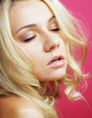 Blond woman over pink background