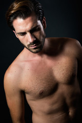Handsome muscular male model posing over black background.