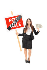 Female realtor holding a sold sign an money