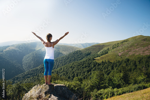 Poster Young woman meditate on the top of mountain