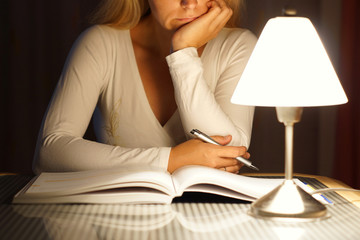 female student is reading book ..late at night