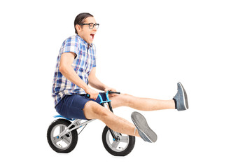 Carefree young guy riding a small bike