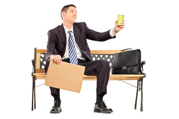 Broke businessman holding a cup and blank banner