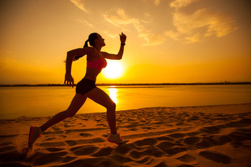 Woman running alone at beautiful sunset in the beach. Summer spo