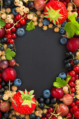 black background for text with fresh garden berries, vertical
