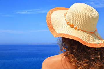 Woman in hat overlooking the seascape closeup