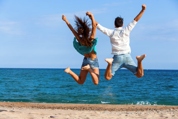 Teen couple jumping giving backs