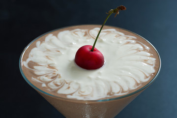 two-layer chocolate dessert in glasses decorated with cherries