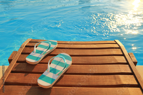 Leinwandbild Motiv Flip flops on wooden sunbed and water