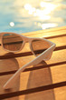 Sunglasses on wooden planks and water on sunset - 68115410