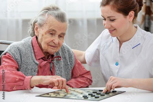 Senior woman playing checkers - 68115829