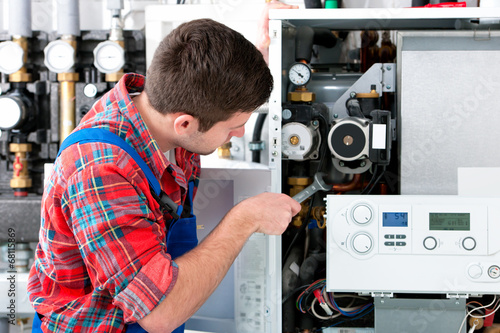 Technician servicing heating boiler - 68115869