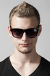 portrait of young man in sunglasses isolated on gray background