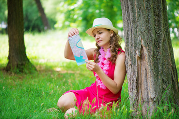 Young woman in pink dress with map at green summer park