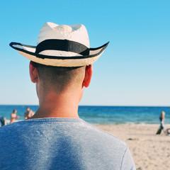 young man with a straw hat on the beach