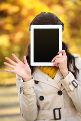 Woman covering her face with digital tablet screen